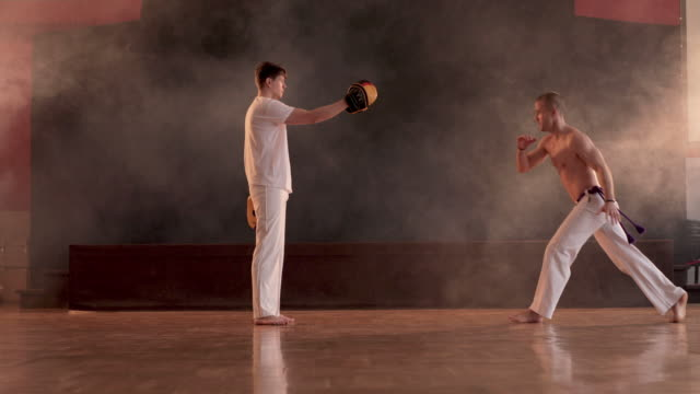 young sportsman practicing on capoeira training with help of his partner. - martial arts stock videos & royalty-free footage