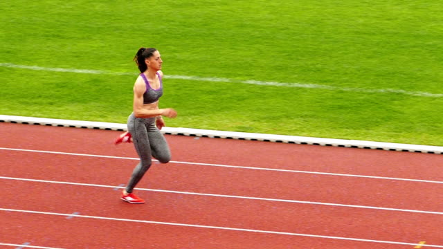 young sportswoman training on running track slow motion video - pista di atletica leggera video stock e b–roll