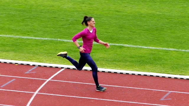 Young Sportswoman training on running track Slow Motion Video