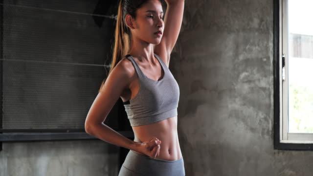 積極的にジムで練習をしている若いスポーティな女性、ジムで女性アスリートのトレーニング。 - 腹筋点の映像素材/bロール
