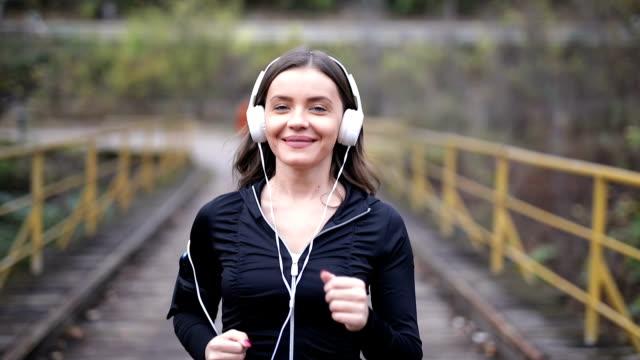 vidéos et rushes de jeune femme sportive faisant le jogging extérieur - joggeuse
