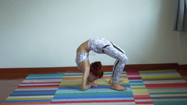 vidéos et rushes de jeune femme sportive pratiquant le yoga, faisant vers le haut faisant l'exercice de yoga à la maison, femme de remise en forme travaillant sur le yoga - flexible