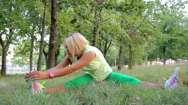 Young sporty woman stretching in the park