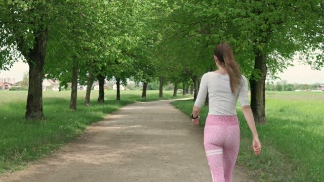 vidéos et rushes de jeune femme sportive marchant dans le parc, vérifiant l'heure sur sa montre - non urban scene