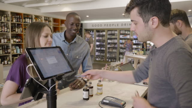 stockvideo's en b-roll-footage met a young straight couple  buy non-alcoholic bitters at the front counter of a neighborhood market and wine shop from a young caucasuan male clerk. - financieel item