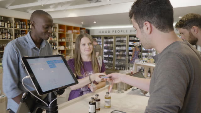 stockvideo's en b-roll-footage met a young straight couple use a credit card to buy non-alcoholic bitters at the front counter of a neighborhood market and wine shop from a young caucasuan male clerk. - financieel item