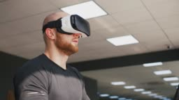 Young strong man exercising on treadmill at the gym, wearing VR glasses, slow motion, close up