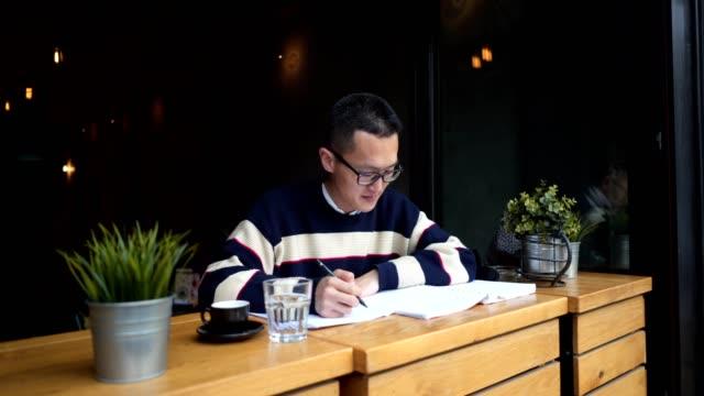 地元のカフェで勉強しながら集中して若い学生 - 30代点の映像素材/bロール