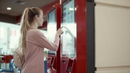 Young student girl is choosing food in fast-food restaurant on big screen