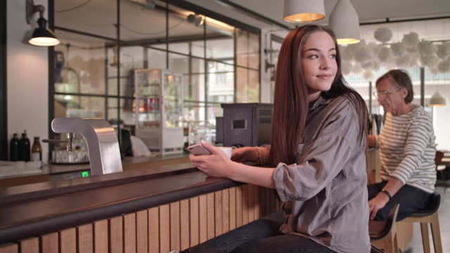 young student girl is online dating in a stylish coffee house using her smartphone and waits for her date to arrive