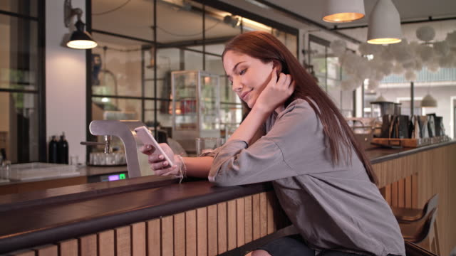 young student girl is online dating in a stylish coffee house using her smartphone
