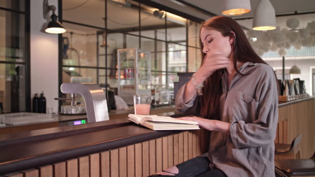 young student girl is reading a book and enjoys a healthy drink in a stylish coffee house - coffee drink stock videos and b-roll footage