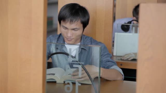 Junger student in Bibliothek