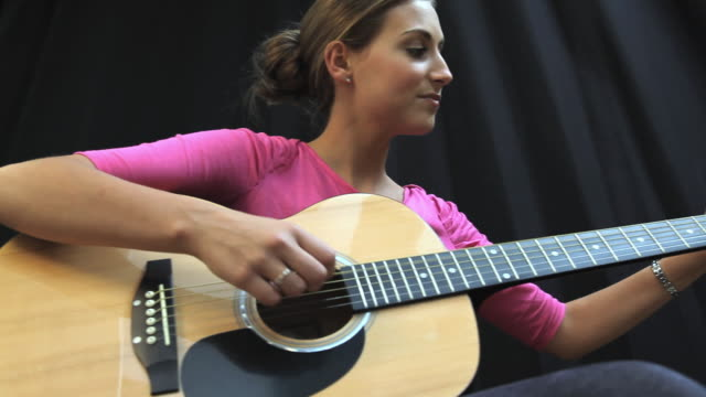 MS LA PAN Young student playing acoustic guitar / London, England