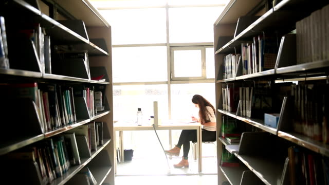 Young student sitting and studying in the library