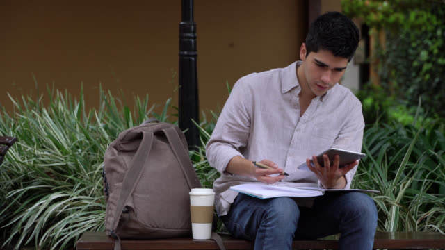vídeos de stock e filmes b-roll de young student studying with a tablet and taking notes while sitting on a bench around the college campus - homens jovens