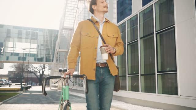 stockvideo's en b-roll-footage met jonge student met een fiets en een kop koffie - vrijetijdskleding