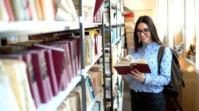 junge schülerin mit büchern und rucksack im bücherregal in der universitätsbibliothek - literatur stock-videos und b-roll-filmmaterial