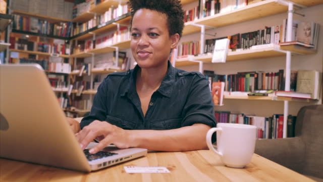 young student working in a public library. - comfortable stock videos & royalty-free footage