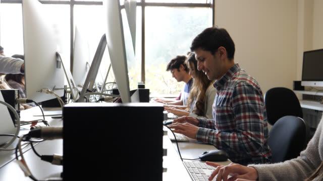 vídeos y material grabado en eventos de stock de jóvenes estudiantes en la universidad en el laboratorio de computación muy centrado en busca - laboratorio de ordenadores