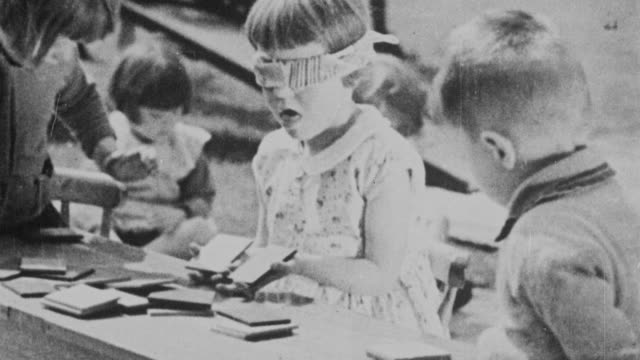 montage young students at school recess playing various games and taking turns going down the slide / united kingdom - 1931年点の映像素材/bロール