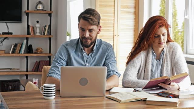 Junge Studenten während des Studiums für ihre Prüfungen zu Hause zusammen.