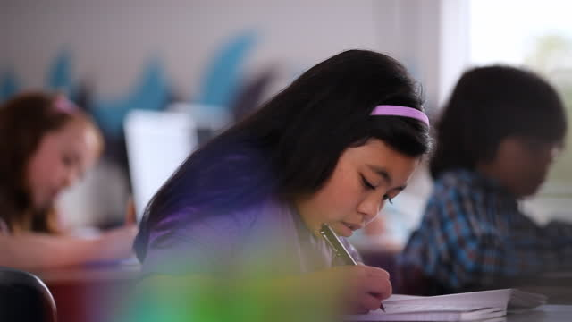 vidéos et rushes de young students diligently take notes during a lesson in their classroom. - wilmington caroline du nord