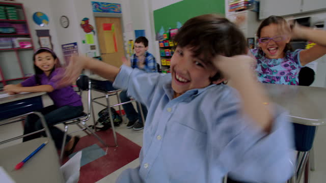 vidéos et rushes de young students get silly as they wave and cheers at their desks during class. - euphorique