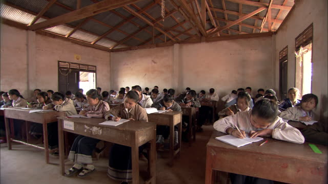 vidéos et rushes de young students in a thai village work intently at their desks in a crowded classroom. - domestic room