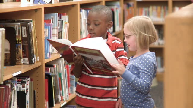 young students in school library sharing a book - primary age child stock videos and b-roll footage