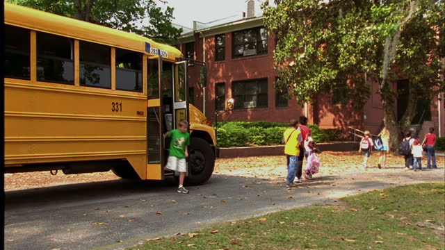 young students leave their school bus and walk toward their school. - disembarking stock videos & royalty-free footage