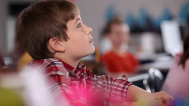 Pan across classroom of students listening