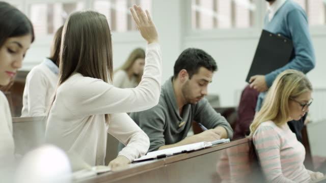 giovani studenti alzando le di rispondere alla domanda - aula universitaria video stock e b–roll