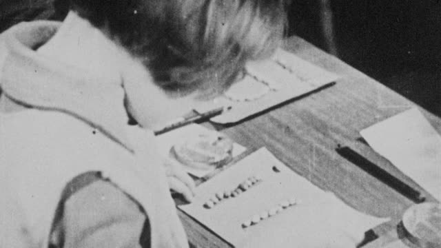 montage young students working on projects at their desks in school / united kingdom - 1931年点の映像素材/bロール