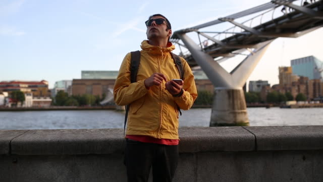 vídeos de stock e filmes b-roll de young stylish adult man with yellow jacket enters to the scene by looking his mobile phone and searching for an address - agenda de telefones