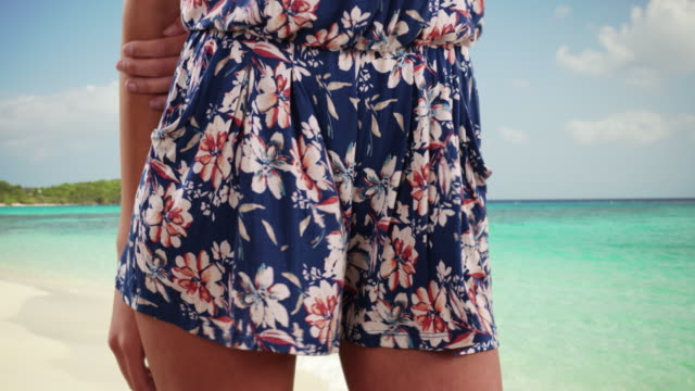 young stylish lady in casual summer wear standing in serene beach setting - hüfte stock-videos und b-roll-filmmaterial