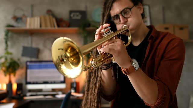 トランペットを演奏ドレッドヘアを持つ若いスタイリッシュなミュージシャン - レゲエ点の映像素材/bロール
