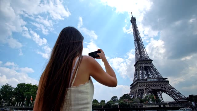 vídeos de stock, filmes e b-roll de a mulher à moda nova olha na torre eiffel - france