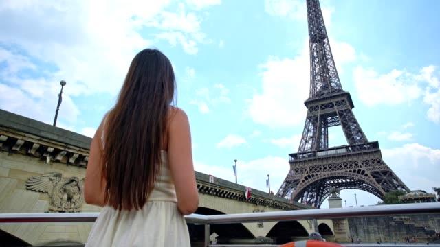 vídeos y material grabado en eventos de stock de joven mujer con estilo mira en la torre eiffel - crucero vacaciones