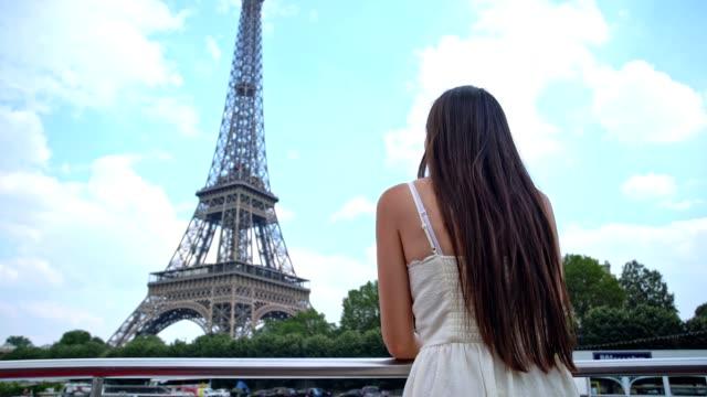 vídeos y material grabado en eventos de stock de joven mujer con estilo mira en la torre eiffel - torre eiffel
