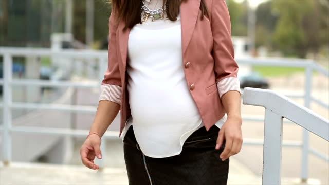 vídeos de stock, filmes e b-roll de jovem mulher de negócios bem sucedido grávida com as mãos cruzadas - cuidado pré natal