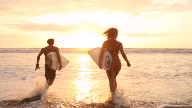 young surfing couple run into waves together, sunrise - ecuadorian ethnicity stock videos and b-roll footage