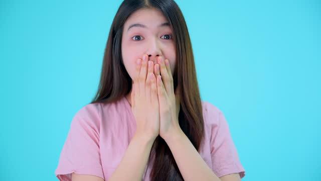 若い驚いたアジアの女性が頬に触れ、驚いて口を開き、不信感と興奮を表現し、青いスタジオの背景 - 20代点の映像素材/bロール
