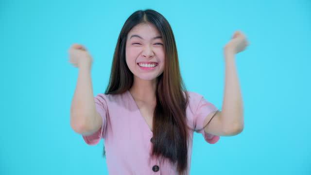 stockvideo's en b-roll-footage met jonge verraste aziatische vrouw die wangen raakt, die mond in verbazing opent, die niet en opwinding, blauwe studioachtergrond uitdrukt - waist up