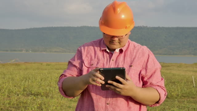 young surveyor working outdoor against of water - surveyor stock videos and b-roll footage