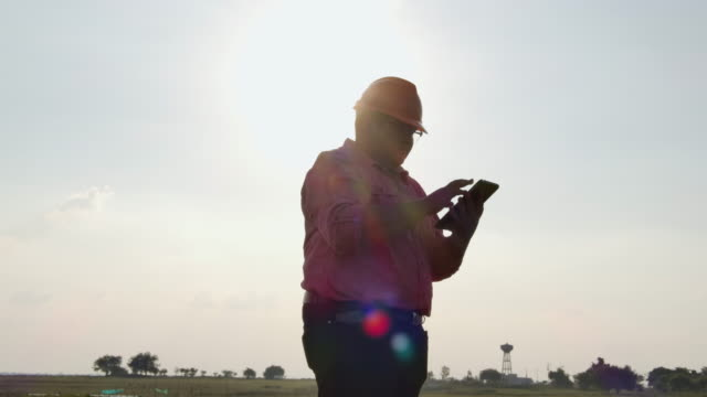vídeos y material grabado en eventos de stock de joven topógrafo que trabaja al aire libre contra el agua - casco protector