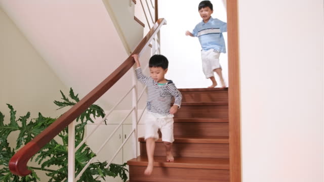 young taiwanese boys descending staircase in home interior - houseplant stock videos and b-roll footage