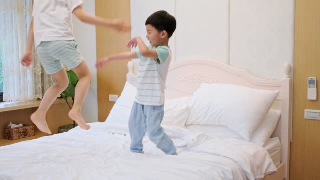 young taiwanese boys jumping on the bed - children only stock videos & royalty-free footage