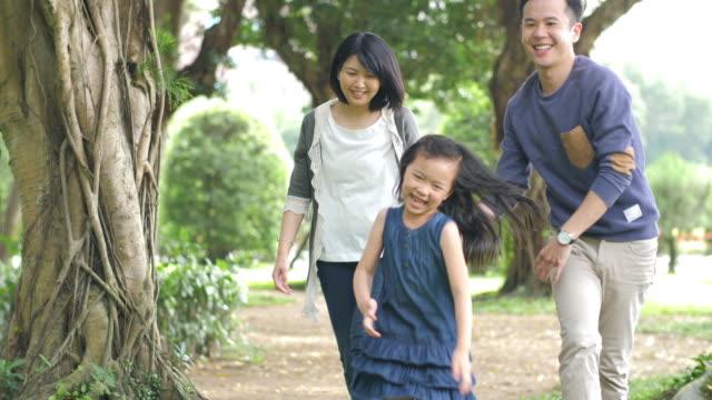 vídeos de stock, filmes e b-roll de família taiwanesa nova que joga o tag com filha - brincadeira de pegar