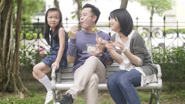 young taiwanese family sitting at the bench - park bench stock videos & royalty-free footage